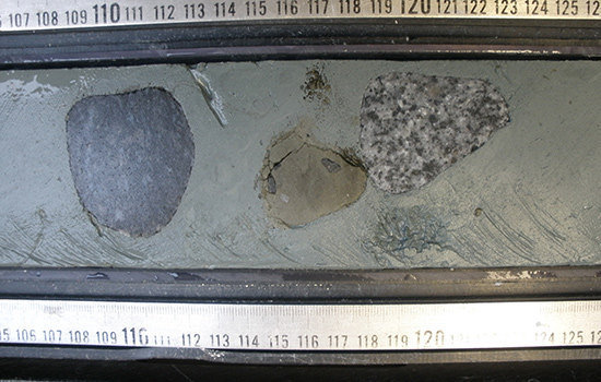 Dropstones can be seen in this sediment core taken from Antarctic coastal waters. Icebergs dragged these large pebbles from the land surface of Antarctica out to sea, where they ultimately fell to the ocean floor. (Image courtesy Saiko Sugisaki)