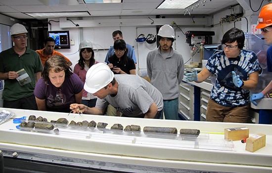 Dr. Beth Orcutt (front, second from left) of Bigelow Laboratory for Ocean Sciences examines oceanic crust samples with Dr. Wolfgang Bach of the University of Bremen, Germany, during IODP Expedition 336 to the Mid-Atlantic Ridge flank. (Photo courtesy of Jennifer T. Magnusson)